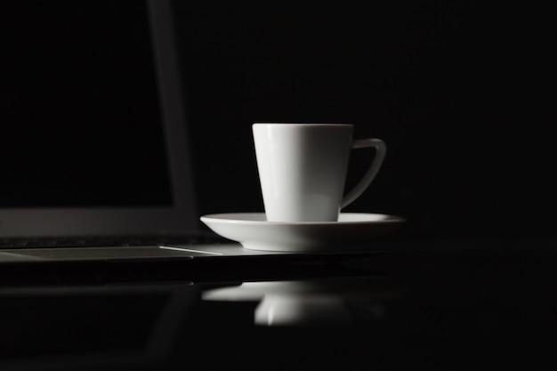 Filiżanka gorącej kawy espresso na drewnianym stole, napar espresso z kawy arabica z laptopem i smartfonem, z bliska strzał biurowy stół z kawową nocą