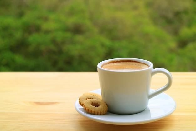 Filiżanka gorącej kawy i ciasteczka na drewnianym stole na zewnątrz z rozmytym zielonym liściem