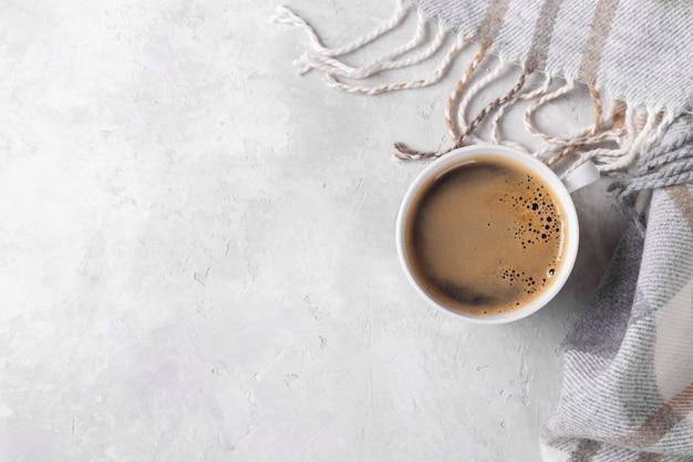 Filiżanka gorącej kawy i kratkę w kratkę