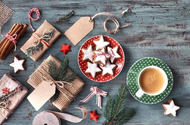 Filiżanka gorącej kawy i opakowanie prezentów świątecznych ciasteczek