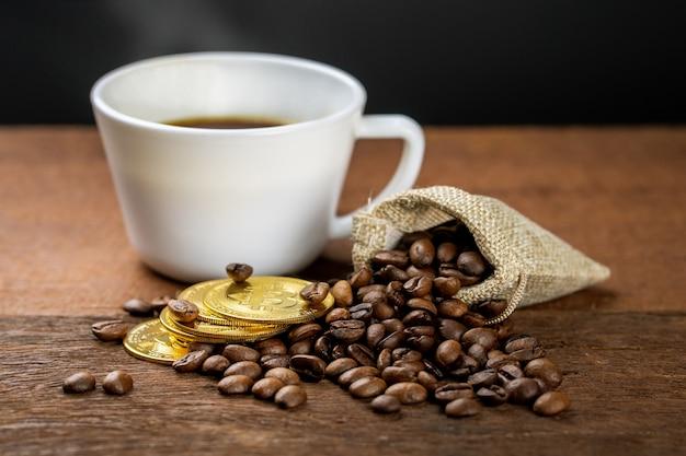 Filiżanka gorącej kawy jest na drewnianym stole, ozdobiona ziarnem kawy i złotą monetą. kawiarnia może zarobić więcej pieniędzy.