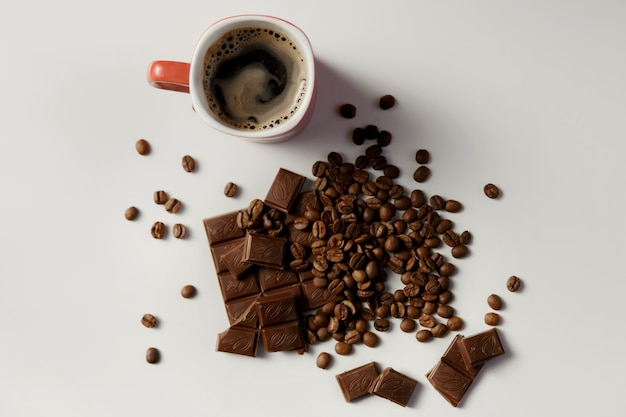 Filiżanka gorącej kawy, kawy ziarnistej i czekolady na białym stole.