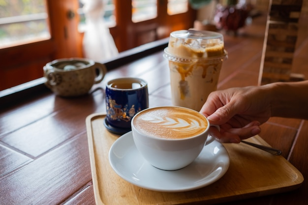 Filiżanka gorącej kawy pod ręką z tłem bokeh, kolor vintage, czas relaksu, poranek