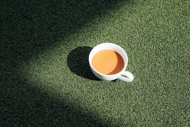 Filiżanka gorącej kawy w zimny poranek, na zielonej trawie z rosą w tle