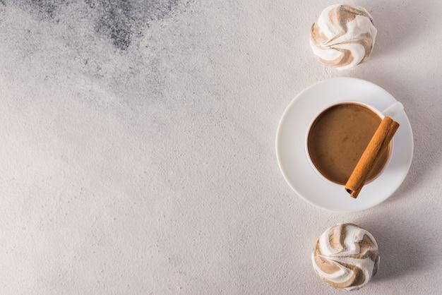 Filiżanka gorącej kawy z mlekiem i słodkimi piankami oraz ciasteczkami na dzień dobry