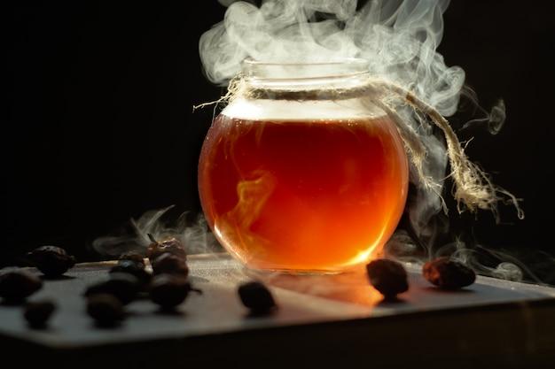 Filiżanka gorącej parującej czarnej puer herbaty, zamyka up. magiczna dymna mikstura lecznicza w butelce.