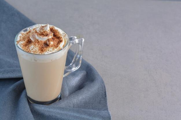 Filiżanka gorącej pysznej kawy ozdobiona kakao na niebieskim materiale.