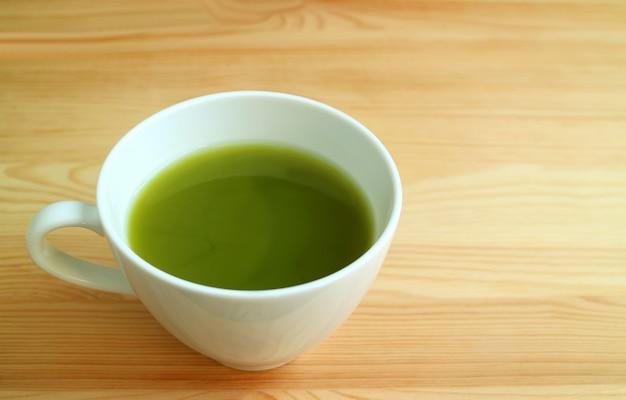 Filiżanka gorącej zielonej herbaty matcha na białym tle na naturalny brązowy drewniany stół