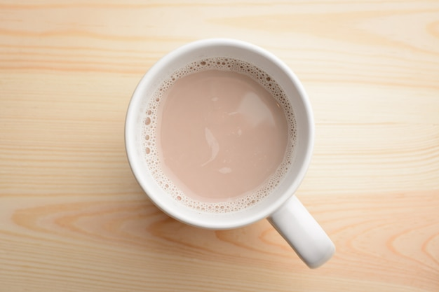 Filiżanka gorący kakao z mlekiem stoi na drewnianym stole