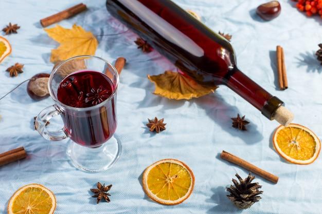 Filiżanka grzanego wina z przyprawami, butelką, suchymi liśćmi i pomarańczami na stole. jesienny nastrój, sposób na ogrzanie się w zimnie, copyspace, poranne światło.