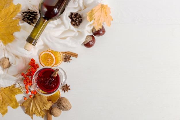 Filiżanka grzanego wina z przyprawami, butelka, szalik, przyprawy, suche liście i pomarańcze na stole. jesienny nastrój, metoda na ogrzanie się na zimno, copyspace.