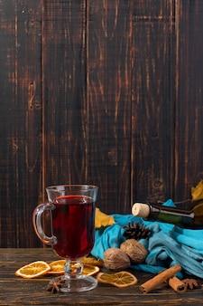 Filiżanka grzanego wina z przyprawami, butelka, szalik, suche liście i pomarańcze na drewnianym stole. jesienny nastrój, metoda na ogrzanie się na zimno, copyspace.