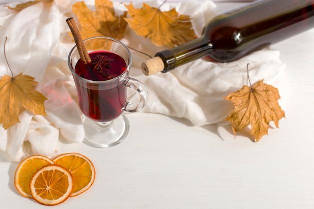 Filiżanka grzanego wina z przyprawami, butelka, szalik, wytrawne liście i pomarańcze na stole. jesienny nastrój, metoda na ogrzanie się na zimno, copyspace.