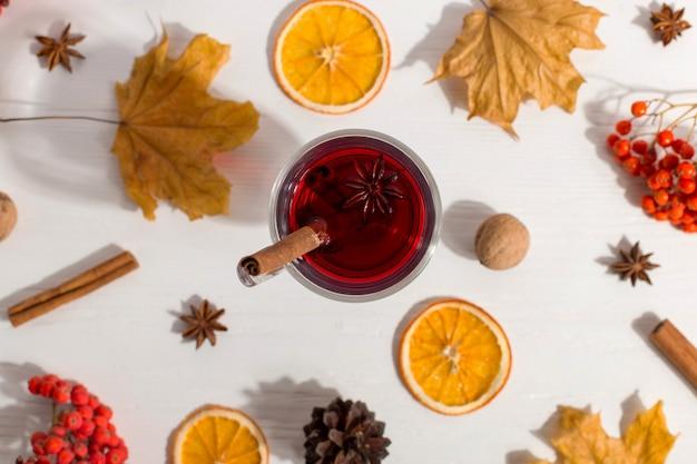 Filiżanka grzanego wina z przyprawami, suchymi liśćmi i pomarańczami na stole. jesienny nastrój, metoda na ogrzanie się w zimnym, porannym świetle, na płasko.