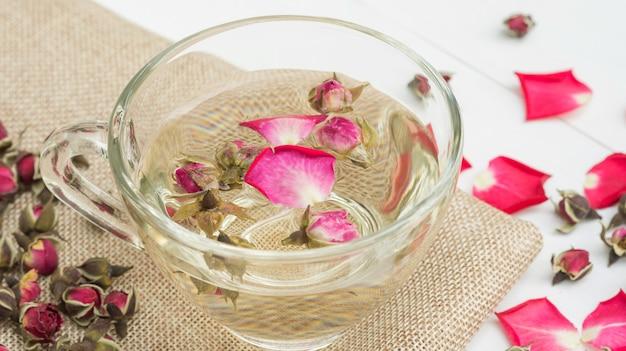 Filiżanka herbaciana menchii róża na białym drewnianym stole.