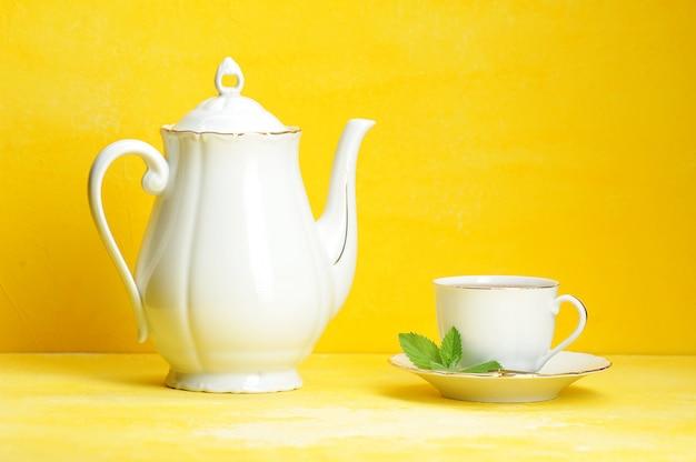 Filiżanka herbaciany czajnik na kolorze żółtym