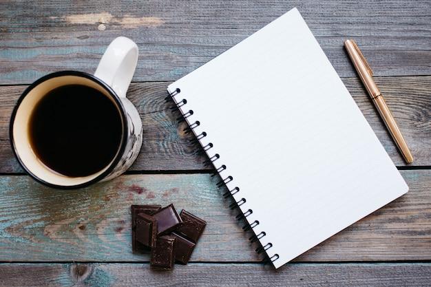 Filiżanka herbata, czekolada i pióro, notatnik na drewnianym stole, flatlay