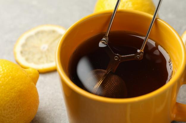 Filiżanka herbata i cytryny na szarość, zbliżenie