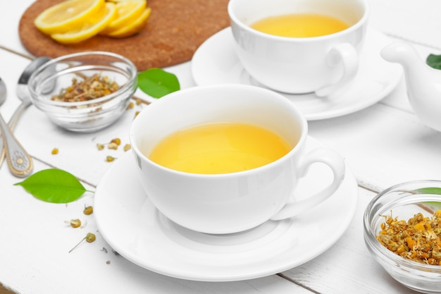 Filiżanka herbata i herbaciani liście na białym drewnianym stole. ścieśniać.