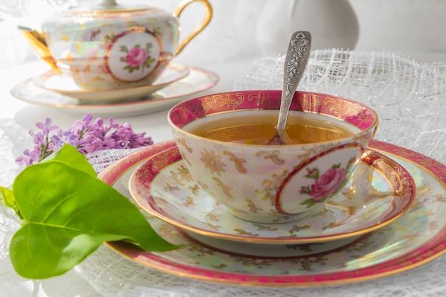 Filiżanka herbata na lekkim stole blisko okno w ranku i wiązki kwiaty z odbitkową przestrzenią