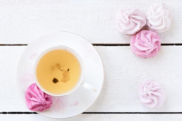 Filiżanka herbata, różowy marshmallow i zielona herbata na bielu. jedzenie. wyroby cukiernicze i napoje