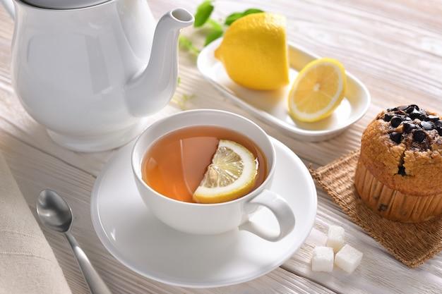 Filiżanka herbata z cytryną i babeczką na bielu stole