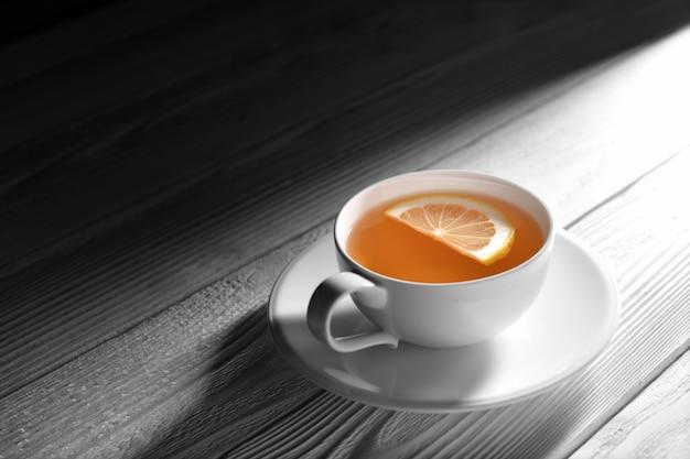 Filiżanka herbata z cytryną na białym drewnianym stole