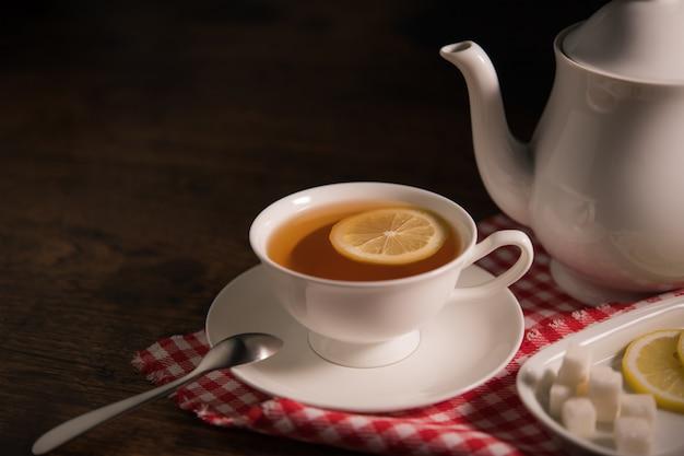 Filiżanka herbata z cytryną na drewnianym stole