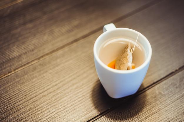 Filiżanka herbata z herbacianą torbą na drewnianym stole