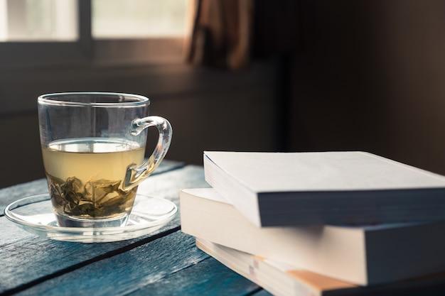 Filiżanka herbata z książką na drewnianym stole