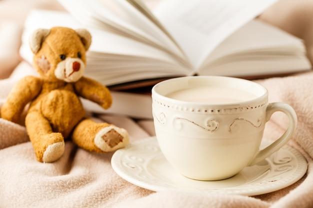 Filiżanka herbata z książką na stołowym zakończeniu