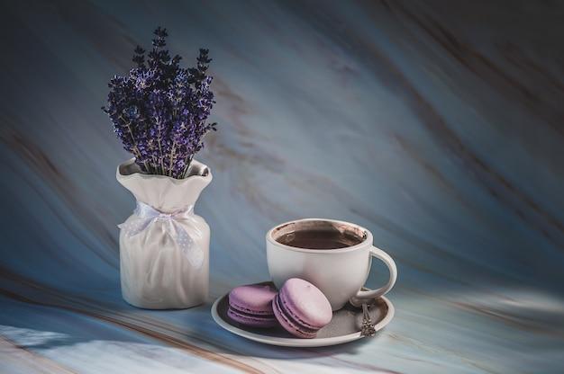 Filiżanka herbata z lawendowymi macarons na teksturze. delikatny francuski deser.
