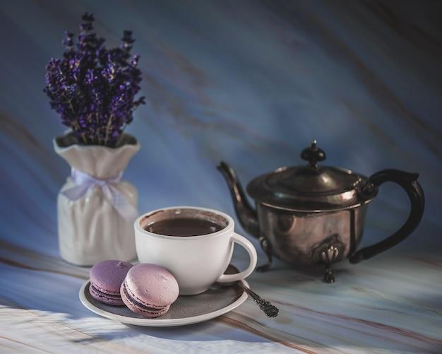 Filiżanka herbata z lawendowymi macarons na teksturze. minimalizm, nieostrość, copyspace. stonowanych poranna niespodzianka.
