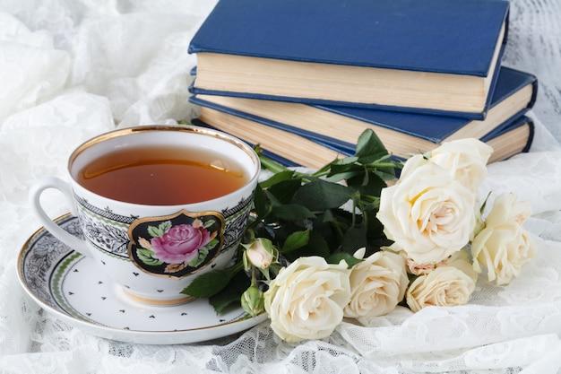Filiżanka herbata z różą na białym drewnianym stole