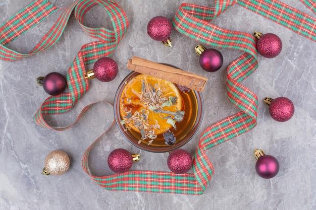 Filiżanka herbaty aromatycznej z prezentem i kokardką na marmurowym backgrond.