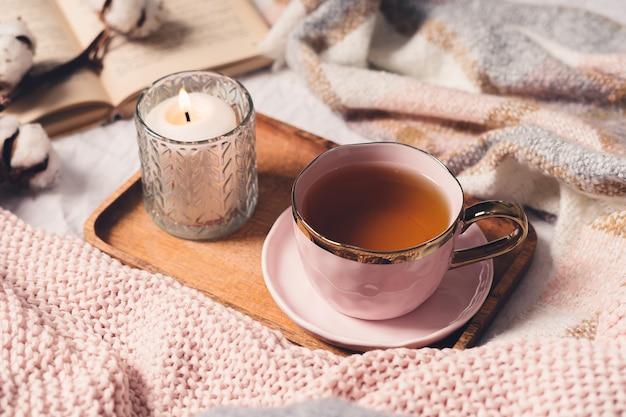 Filiżanka herbaty, bawełna, przytulna, książka, świeca. przytulna koncepcja jesień zima.