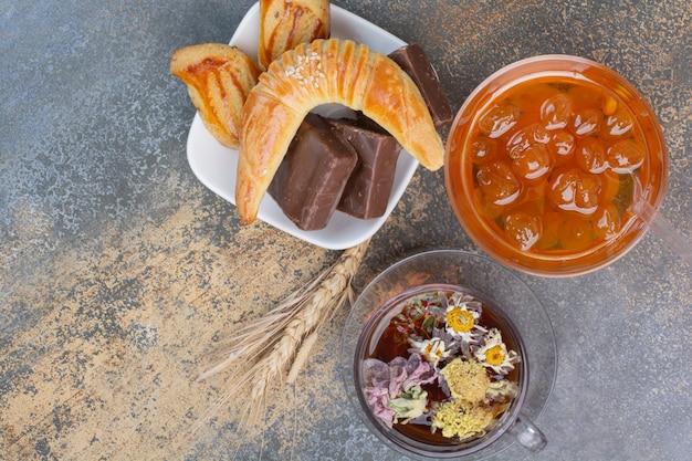 Filiżanka herbaty, ciasteczka i dżem jagodowy na powierzchni marmuru