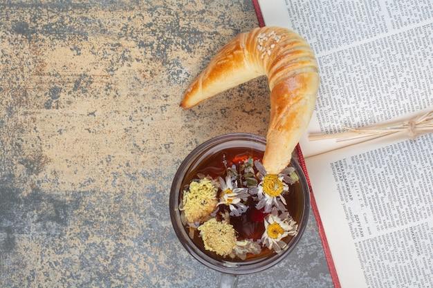 Filiżanka herbaty, ciasteczka i książki na powierzchni marmuru.