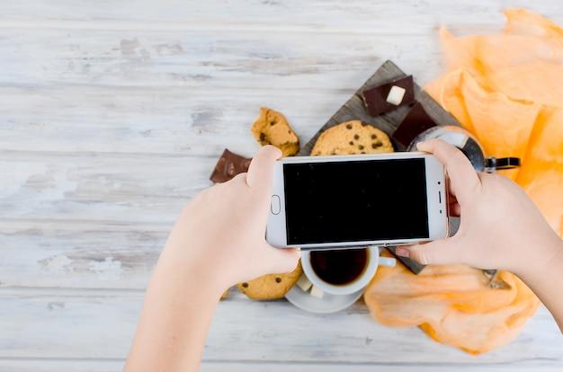 Filiżanka herbaty, ciastka na białym drewnianym stole i ręka bierze fotografię