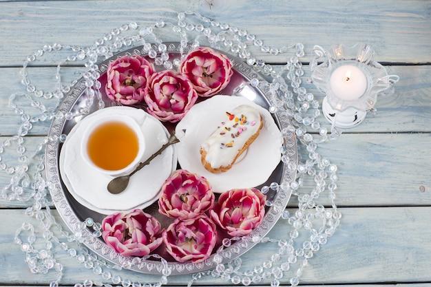 Filiżanka herbaty, ciasto, koraliki, świecznik ze świecą i siedem pąków tulipana