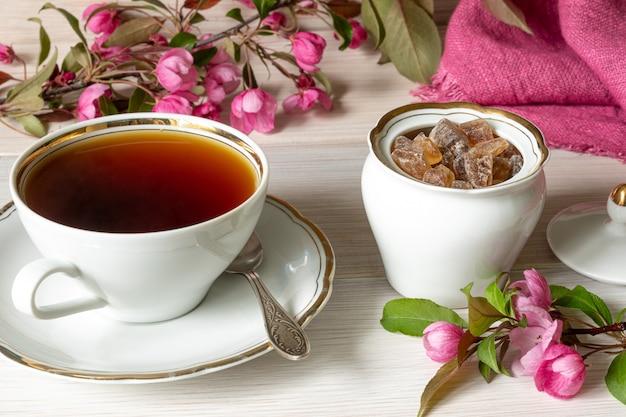Filiżanka herbaty, cukier w kostkach w białej cukiernicy obok różowych kwiatów na białym drewnianym stole.