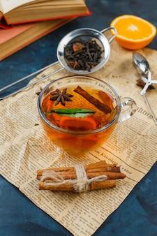 Filiżanka herbaty, cynamon i sitka do herbaty z gazetą, pomarańczą i książką na powierzchni niebieskiego marmuru