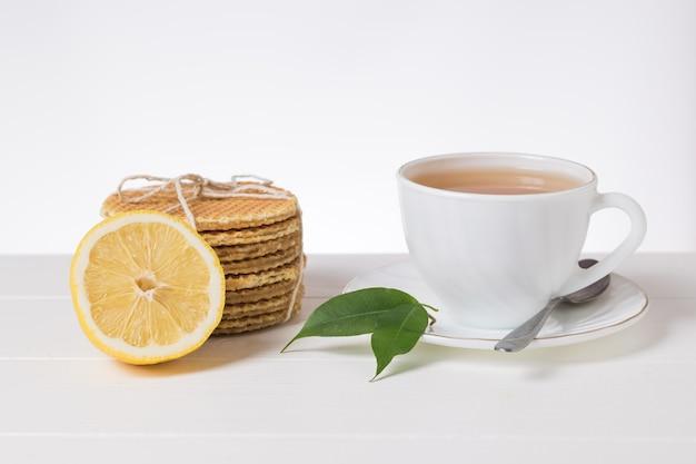 Filiżanka herbaty, cytryny i gofrów na białym stole na jasnym tle. domowe ciasta z herbatą.