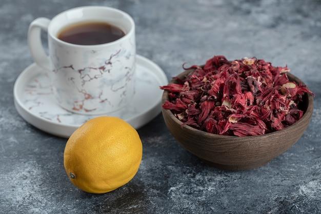 Filiżanka herbaty, cytryny i miska suszonych kwiatów na marmurowym stole.