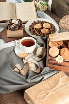 Filiżanka herbaty, czekoladowe pralinki i taca ciastek