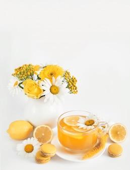 Filiżanka herbaty daisies z plasterkiem cytryny i świeżymi kwiatami rumianku w wazonie