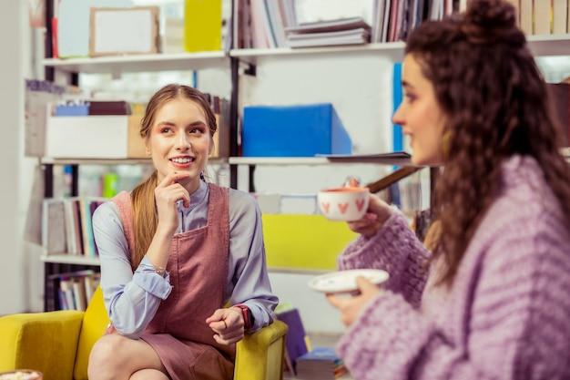 Filiżanka herbaty. długowłosa dziewczyna w różowej sukience prowadzi ciekawą rozmowę ze swoją ciemnowłosą przyjaciółką