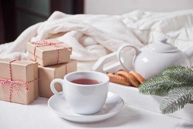 Filiżanka herbaty, domowe ciasteczka, świąteczne pudełka na prezenty i biały świąteczny wystrój.