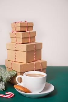 Filiżanka herbaty, domowe ciasteczka, świąteczne pudełka na prezenty i świąteczny wystrój na zielono.