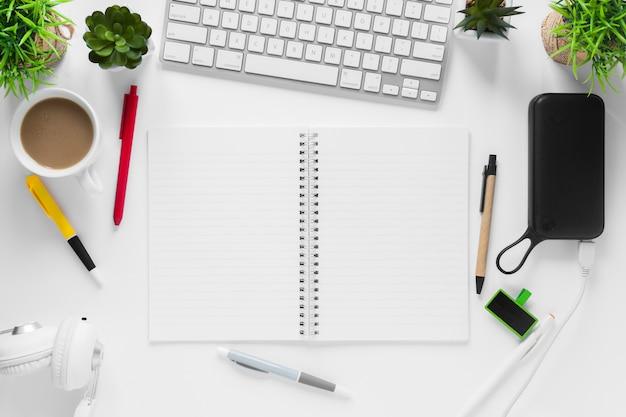 Filiżanka herbaty; doniczki; notes spiralny; kubek herbaty i długopisy na białym biurku